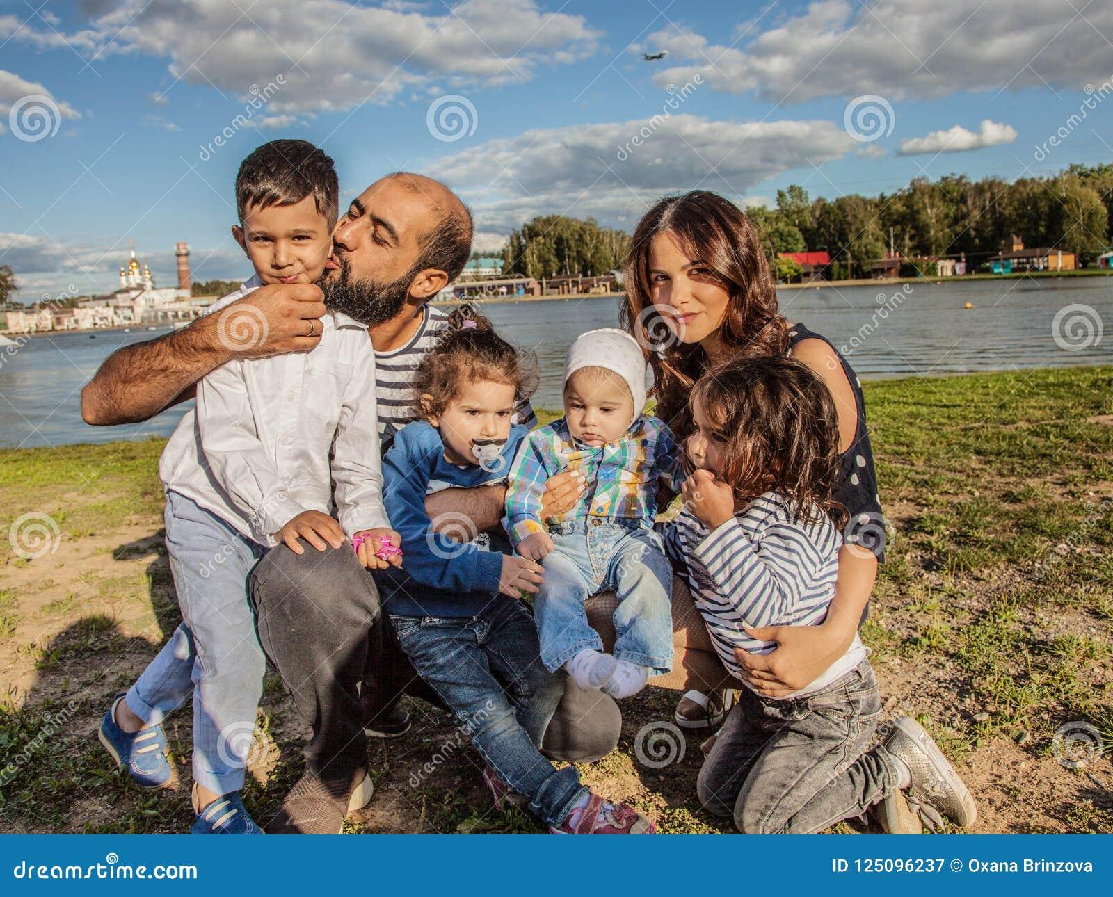 Glückliche Familie in der Natur auf dem Hintergrund von einem schönen See Töchter des Muttervatis zwei und zwei Söhne