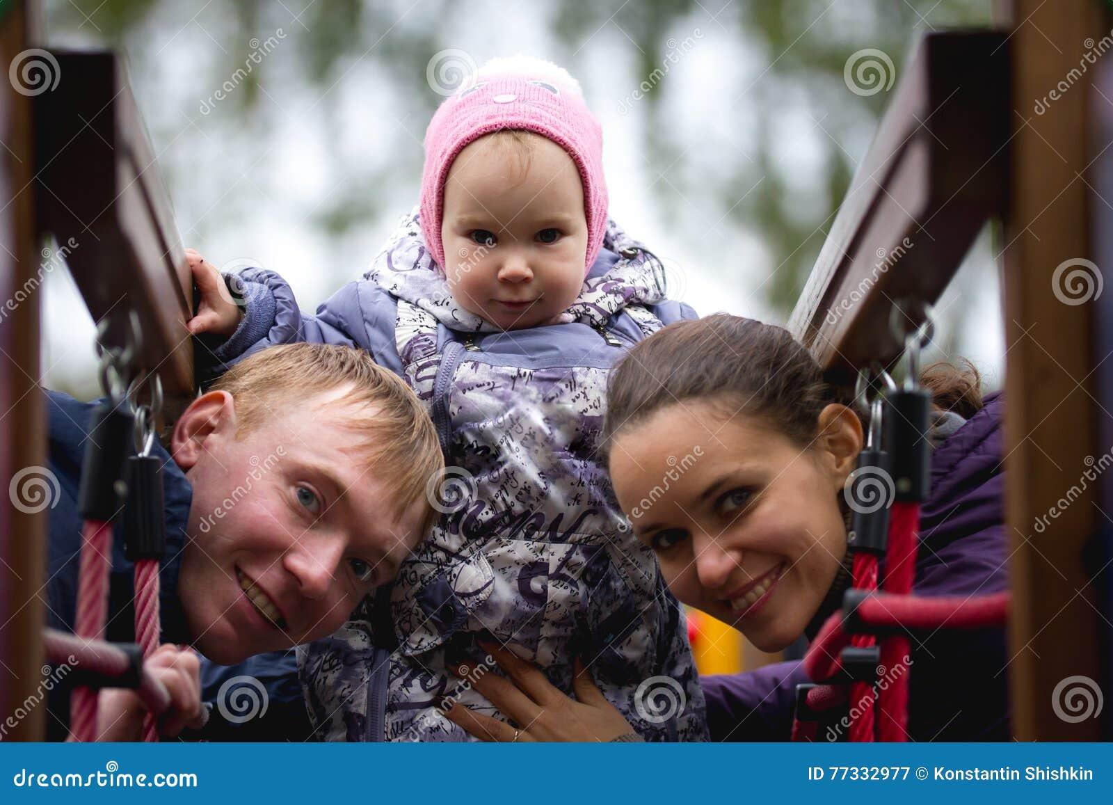 Glückliche Familie: Der Vater, Mutter und kinder- kleines Mädchen, die in Herbst gehen, parken: mamy, Vatibaby, das am Spielplatz