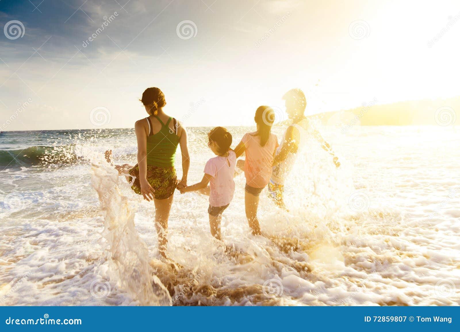 Glückliche Familie, die auf Strand bei Sonnenuntergang spielt