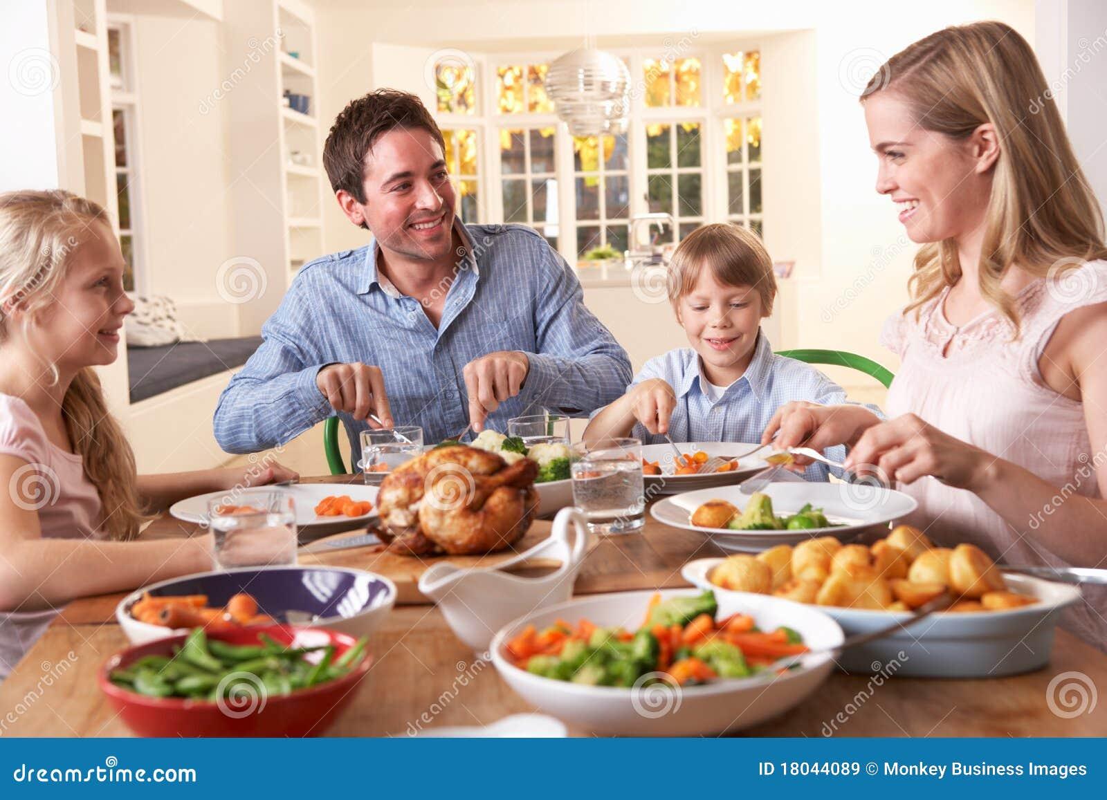 Glückliche Familie, die Bratenhuhn am Tisch zu Abend isst