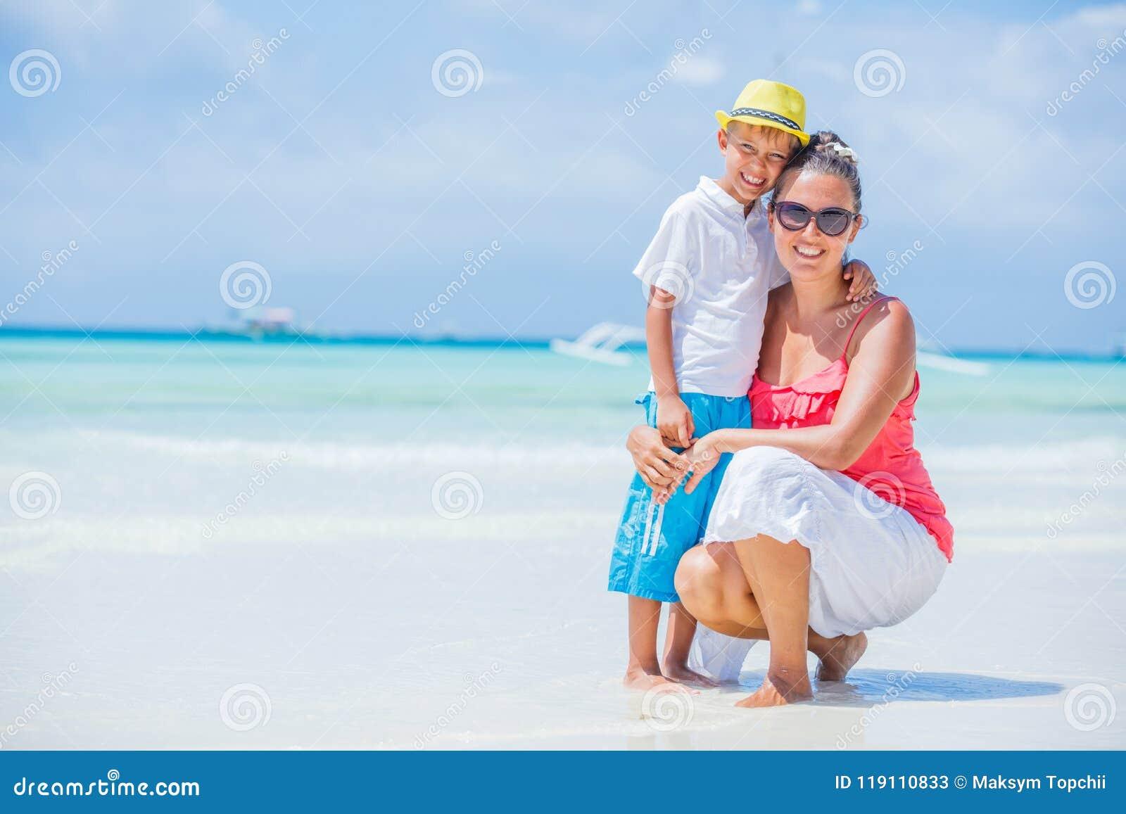 Glückliche Familie, die am Strand im Sommer stillsteht Mutter mit dem Jungen, der auf dem Strand stillsteht Junge Mutter und ihr