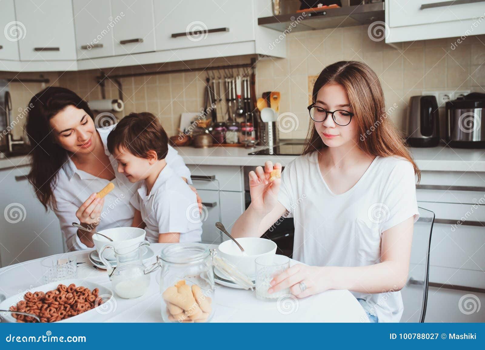 Glückliche Familie, die zu Hause frühstückt Mutter mit zwei Kindern, die morgens in der modernen weißen Küche essen