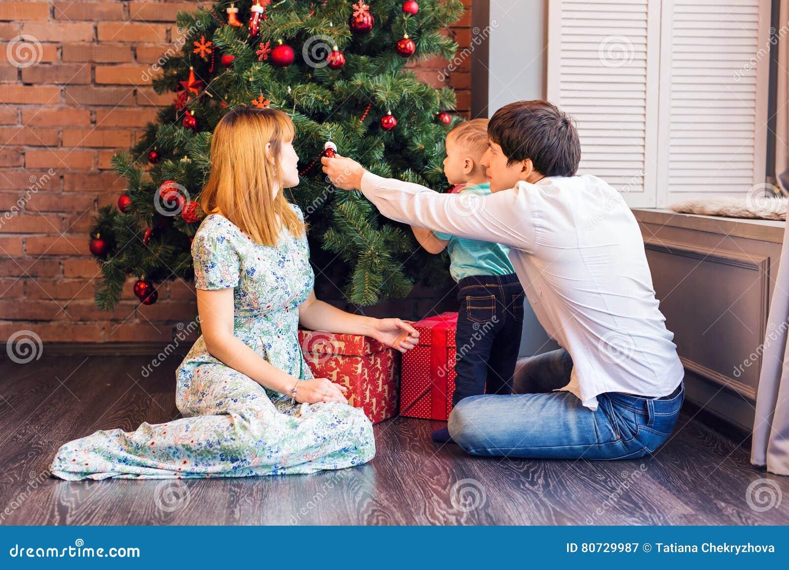 Glückliche Familie, die zu Hause mit Weihnachtsbällen spielt
