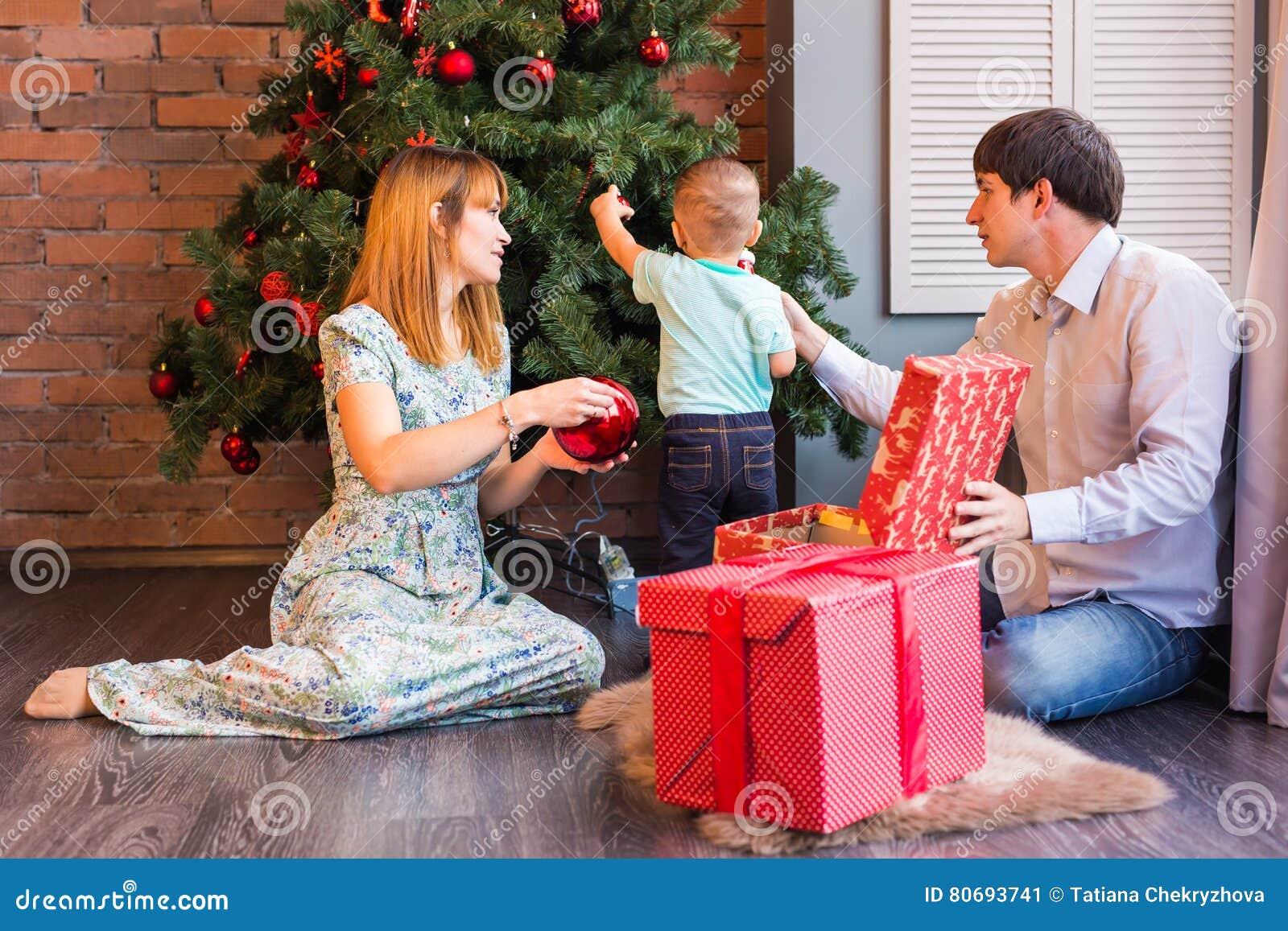 Glückliche Familie, die zusammen Weihnachtsbaum verziert Vater, Mutter und Sohn Nettes Kind zicklein