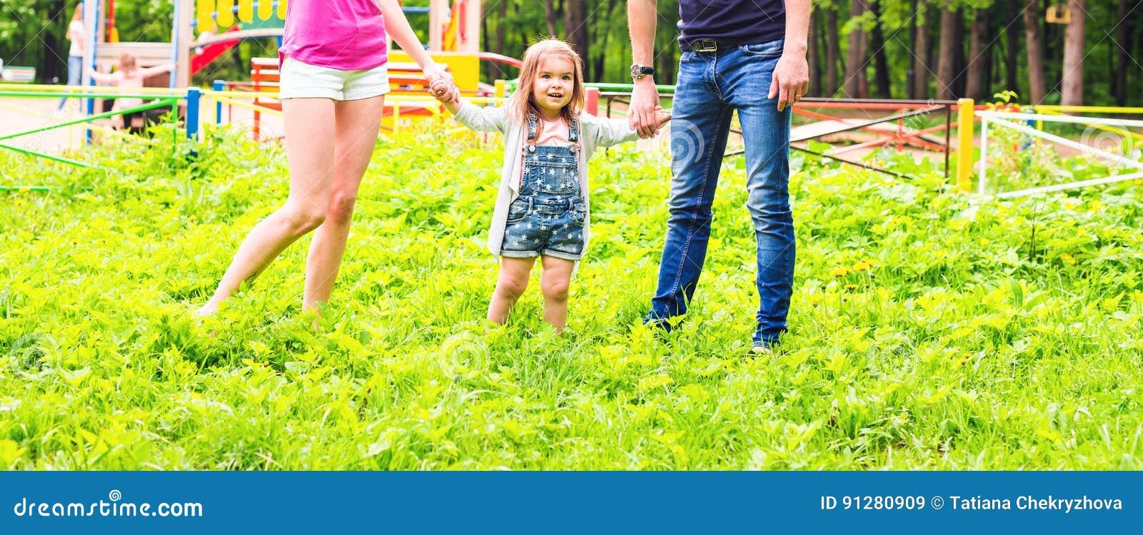 Glückliche Familie im Park Glücklicher Weg der Mutter, des Vatis und des Babys Das Konzept einer glücklichen Familie Eltern halte