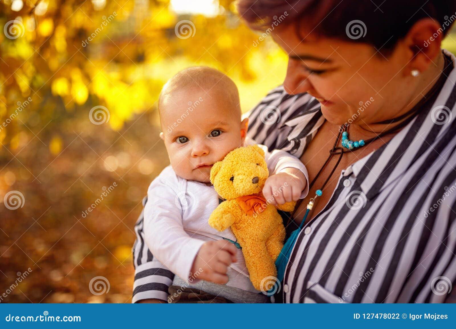 Glückliche Familie - junge Mutter und Baby im Herbst parken