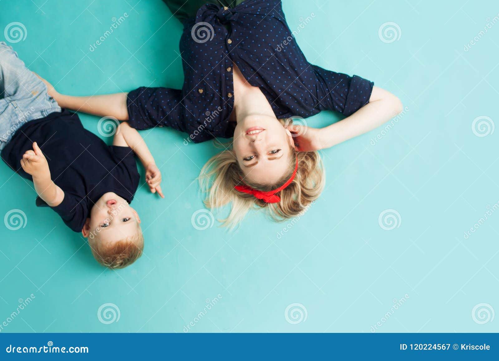 Glückliche Familie Junge schöne blonde Frau mit Spaßsohn Lüge, die Ansicht von der Spitze