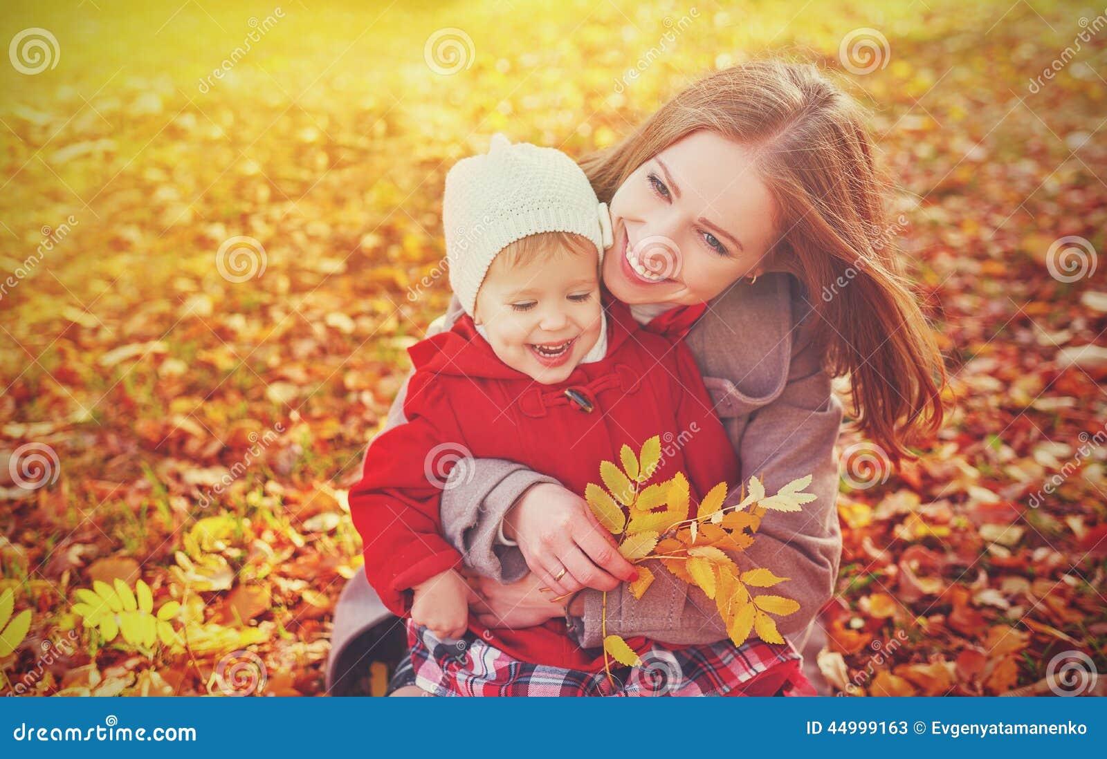 Glückliche Familie: kleine Tochter der Mutter und des Kindes spielen die Umarmung auf Herbst