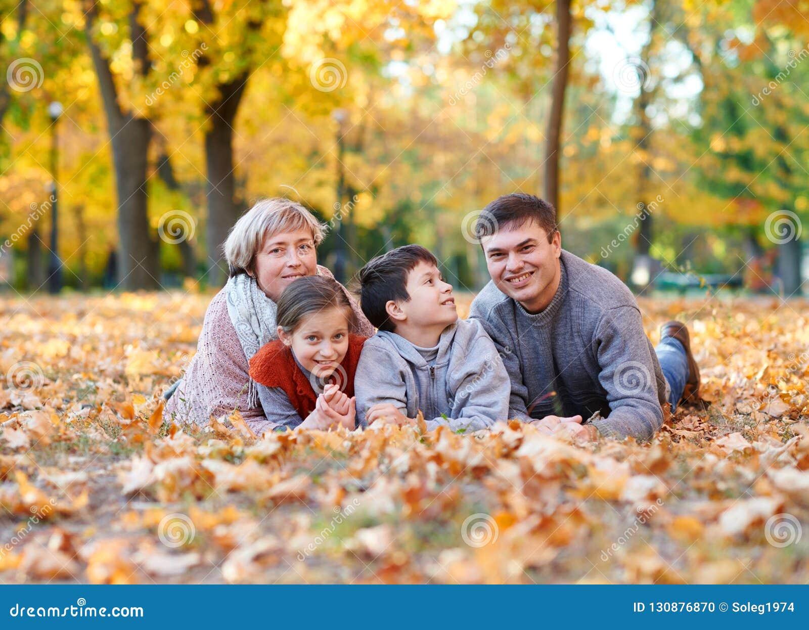 Glückliche Familie liegt im Herbststadtpark auf gefallenen Blättern Kinder und Eltern, die Spaß aufwerfen, lächeln, spielen und h