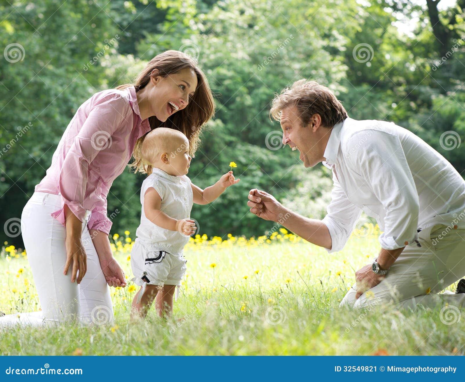 Glückliche Familie mit dem Kind, das dem Vater Blume gibt