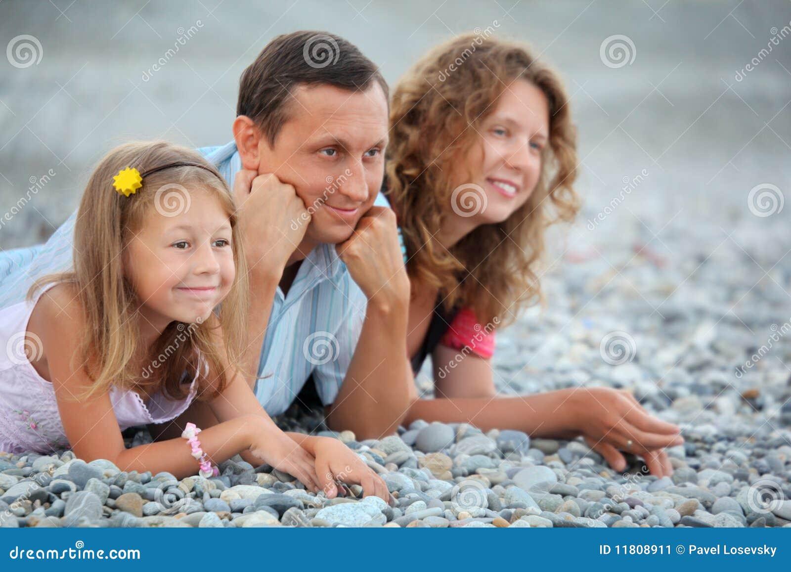 Glückliche familie mit dem kleinen mädchen das auf steinigem strand
