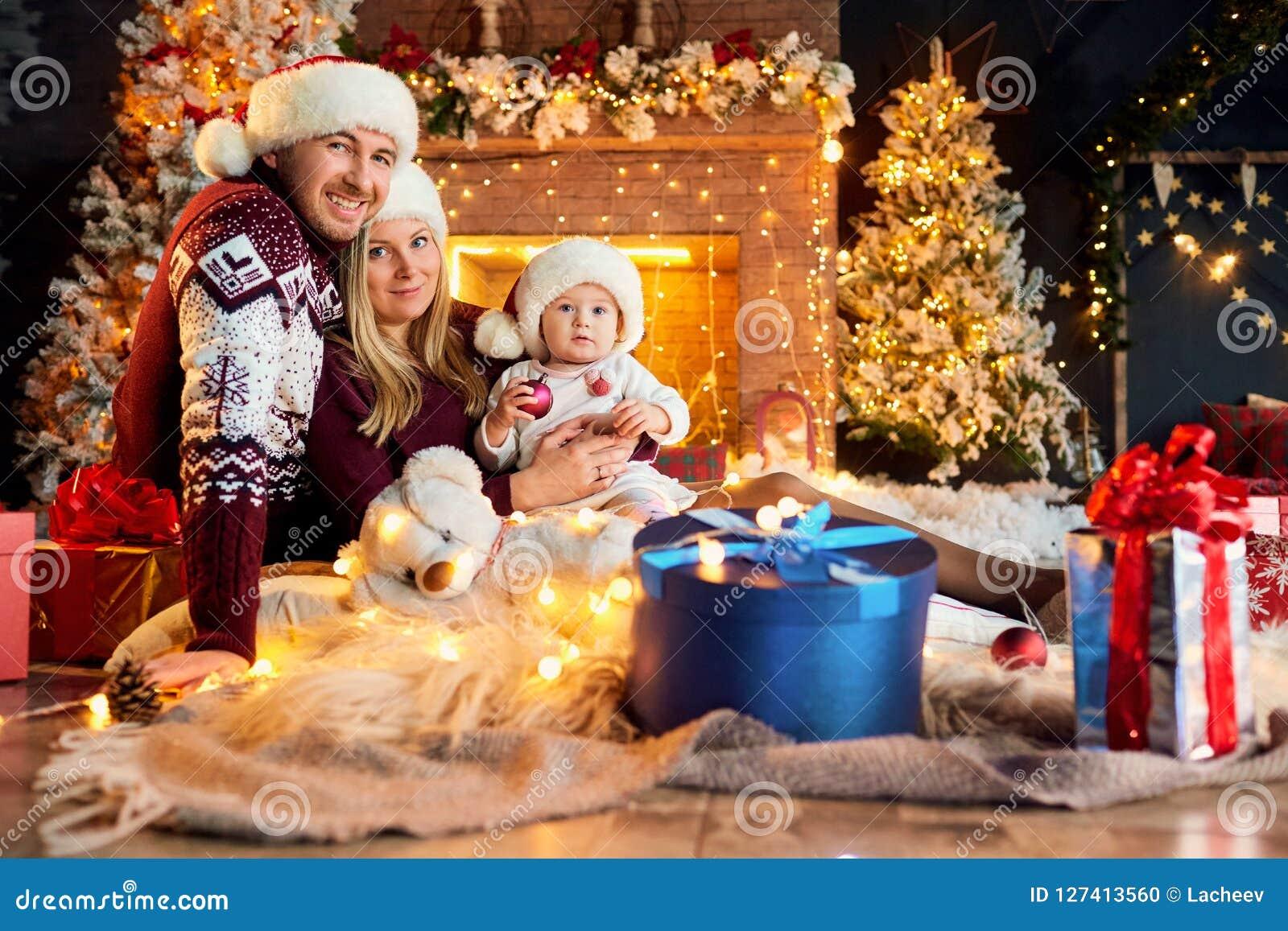 Glückliche Familie mit einem Baby in einem Weihnachtsraum