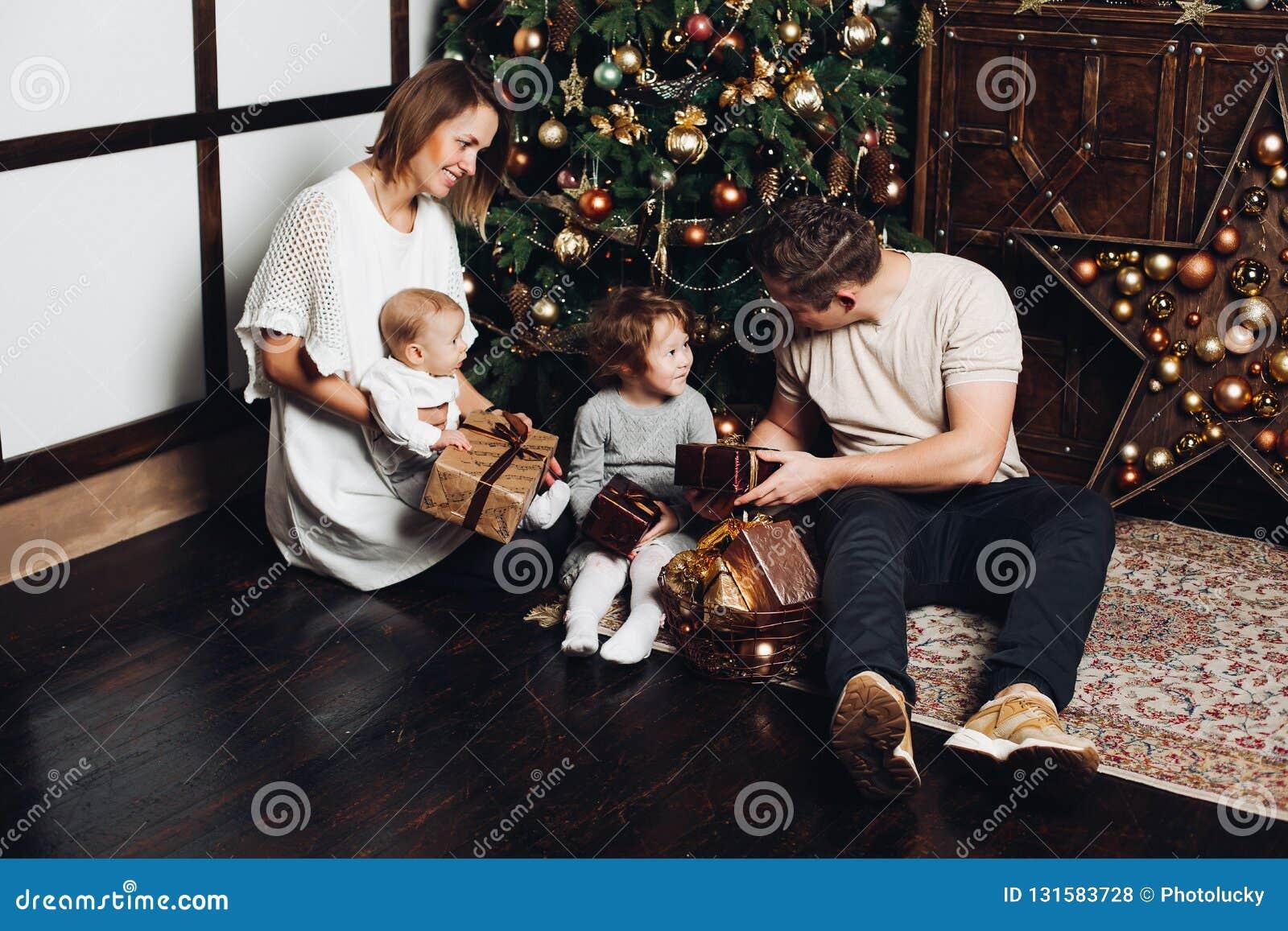 Glückliche Familie mit Weihnachtsgeschenken an verziertem Tannenbaum