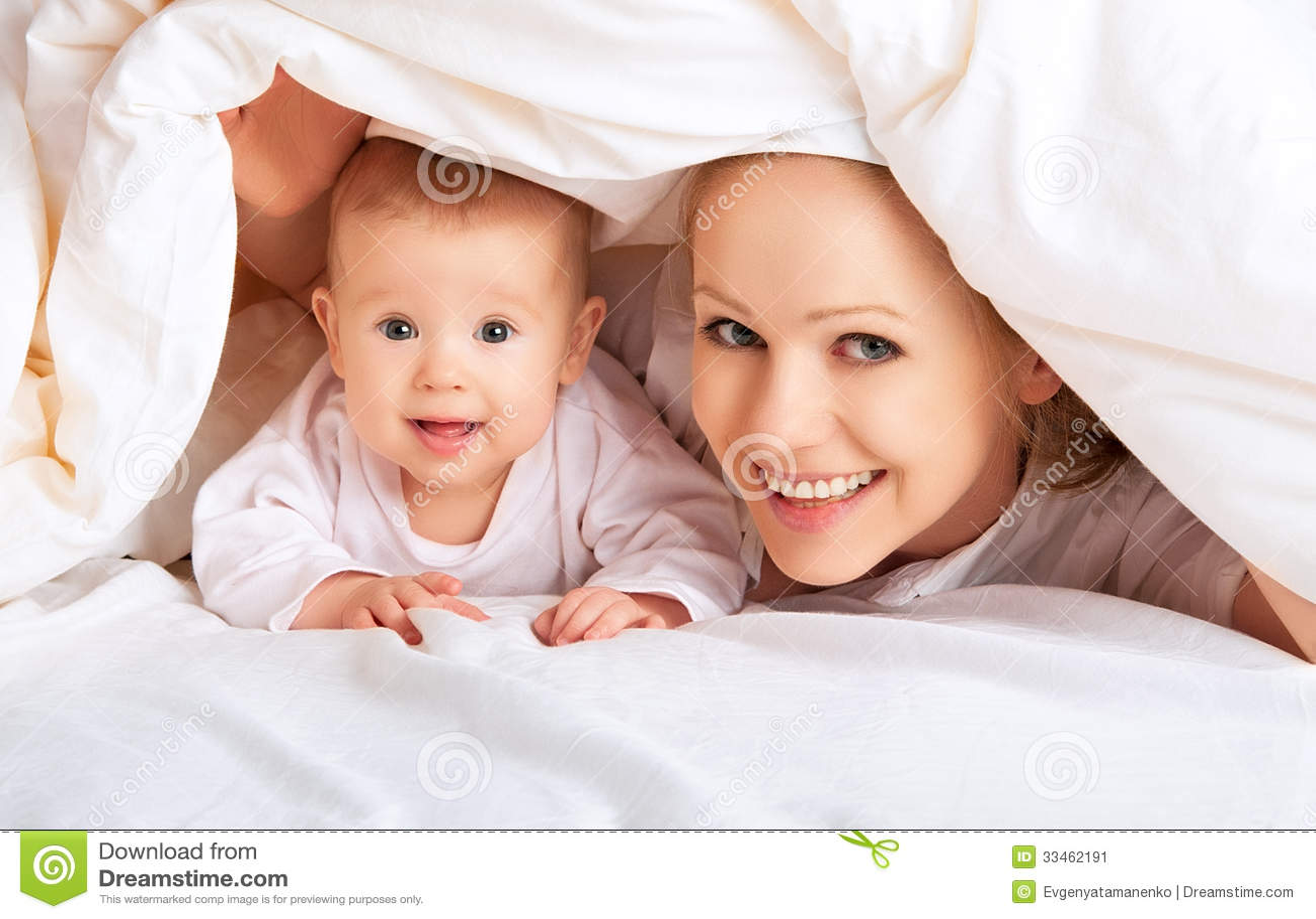 Glückliche Familie. Mutter und Baby, die unter Decke spielen