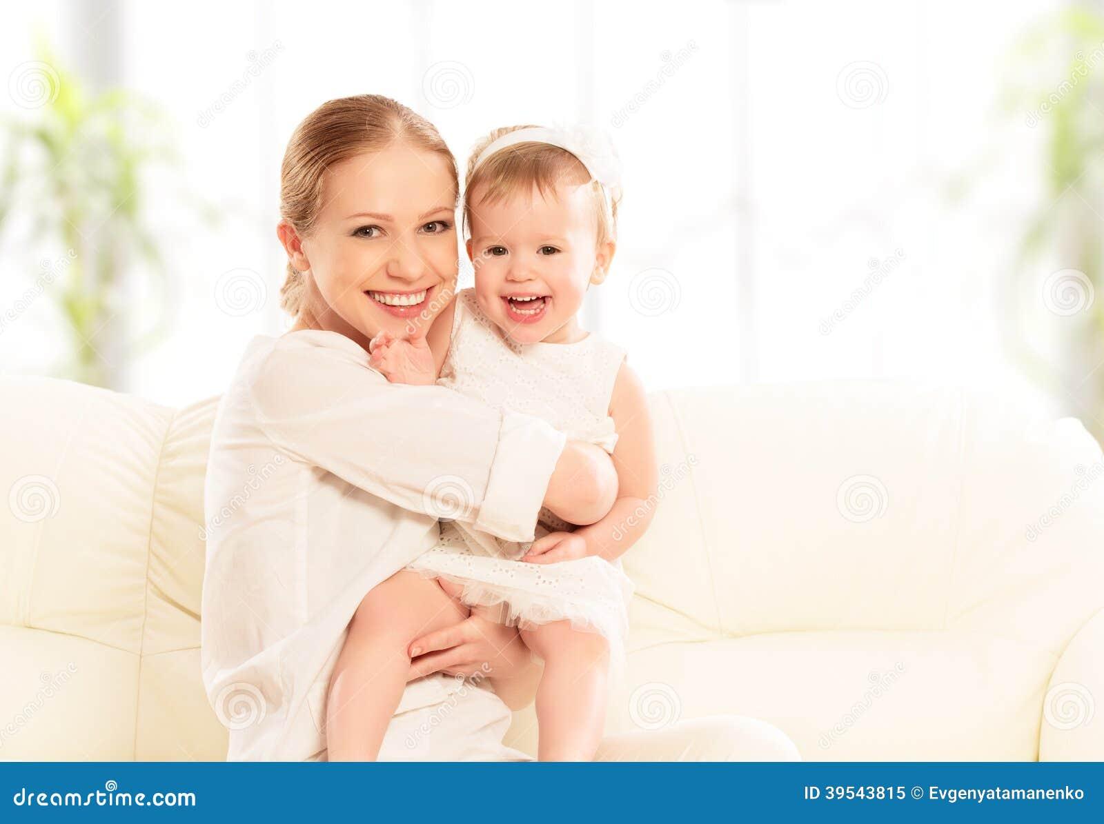 Glückliche Familie. Mutter- und Babytochterspiele, Umarmen, küssend