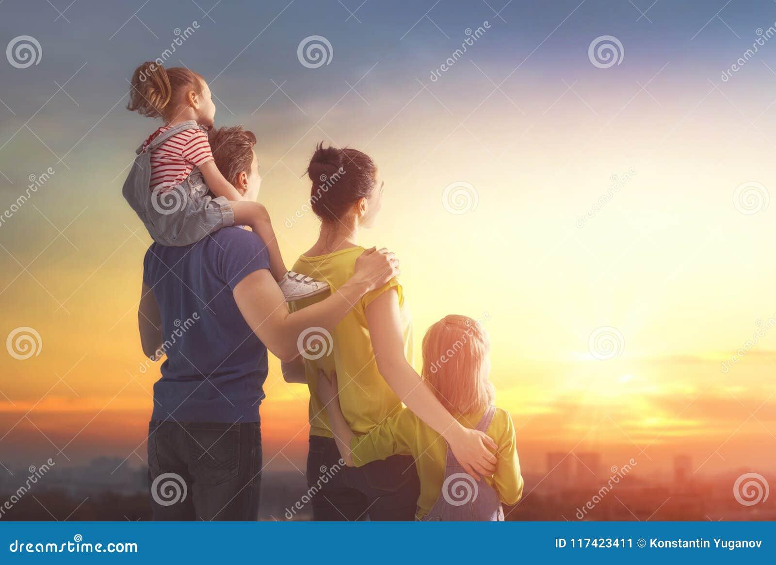 Glückliche Familie am Sonnenuntergang