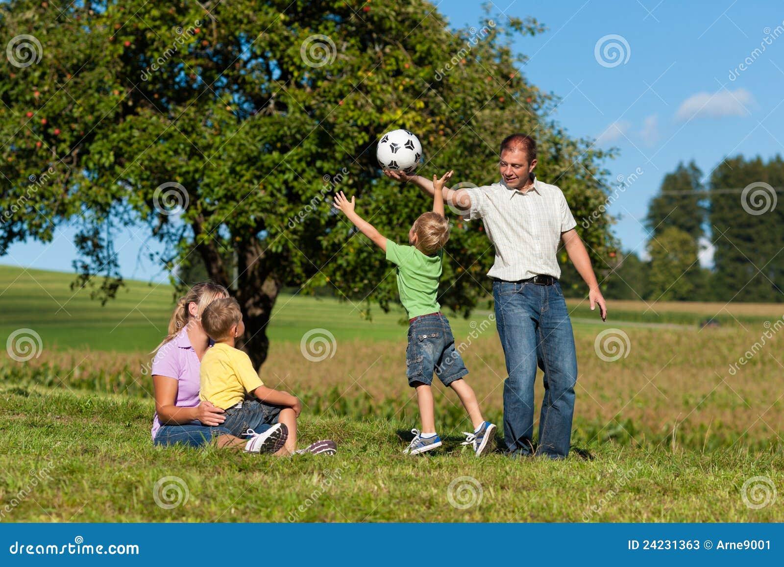 Glückliche Familie spielt Fußball am Sommer