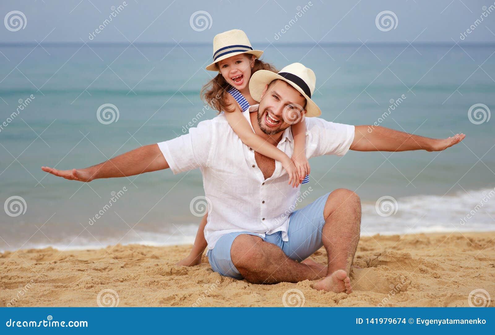 Glückliche Familie am Strand Vater- und Kindertochterumarmung in Meer