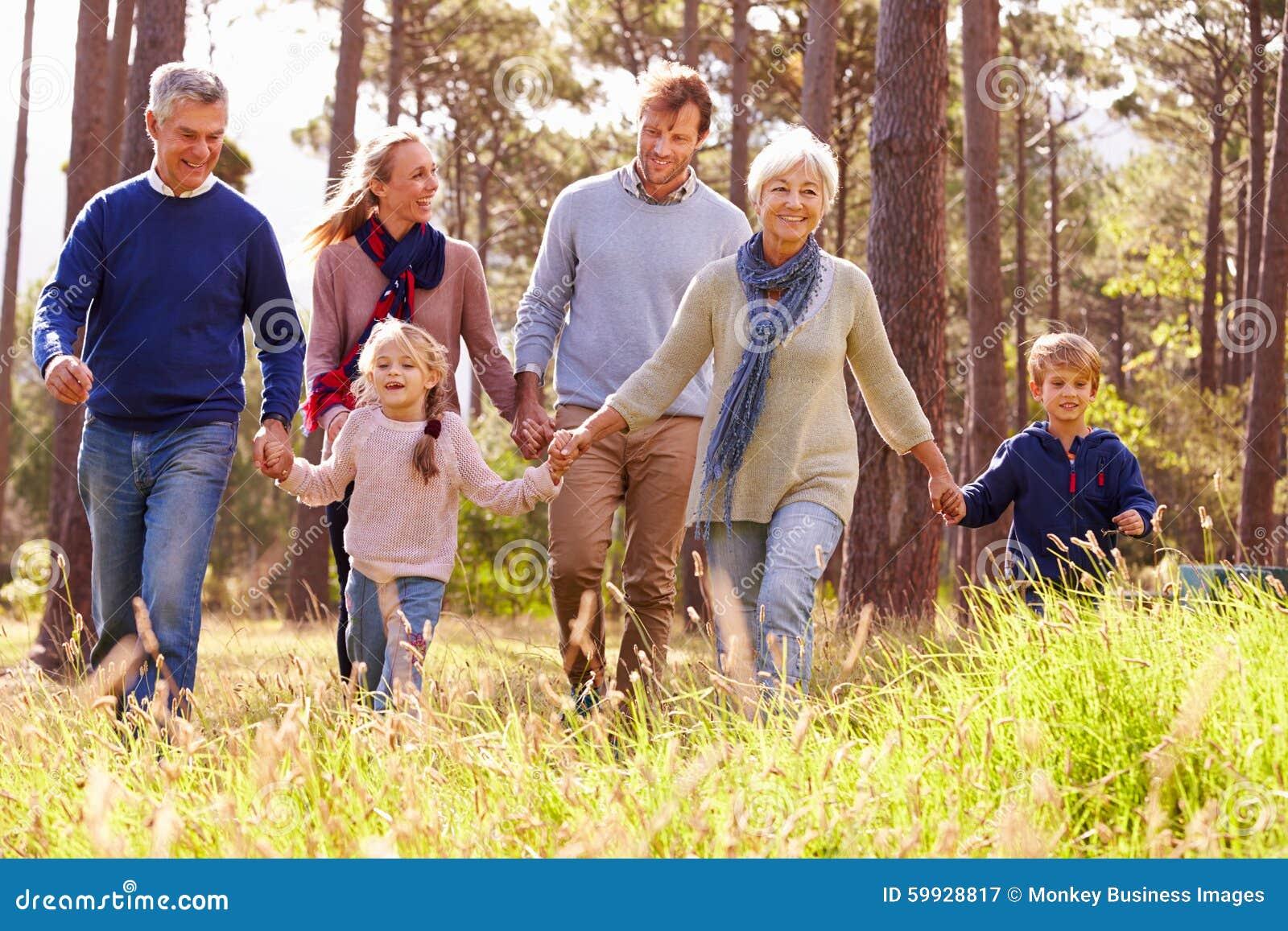 Glückliche Familie von mehreren Generationen, die in die Landschaft geht