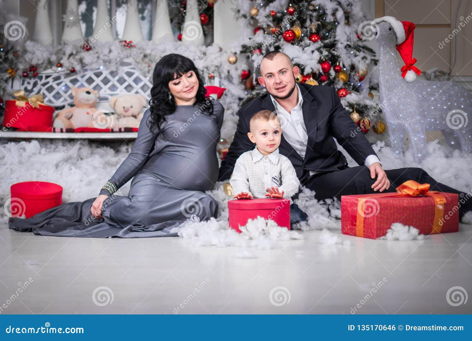 Glückliche Familie Weihnachtsoffenes Geschenk schwangerer Mutter
