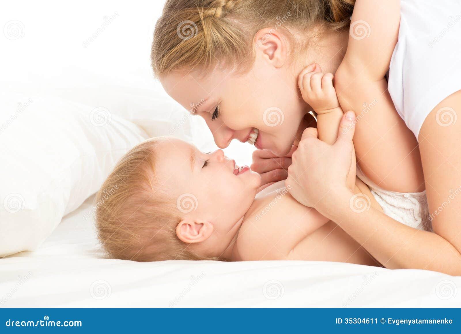 Glückliche Familienmutter und -baby, die das Spaßspielen, lachend auf Bett hat