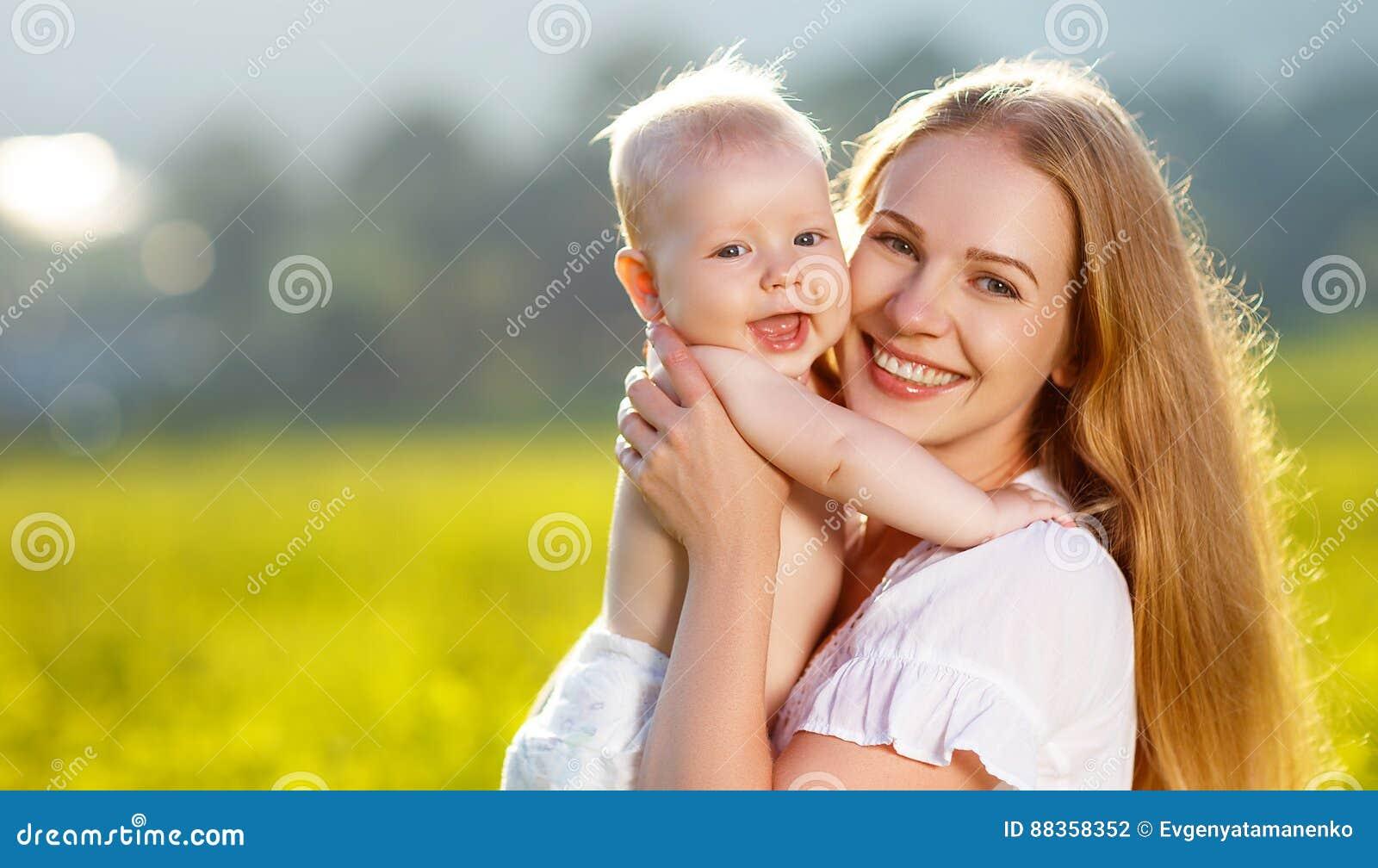 Glückliche Familienmutter und -baby, die Natur im Sommer umarmt
