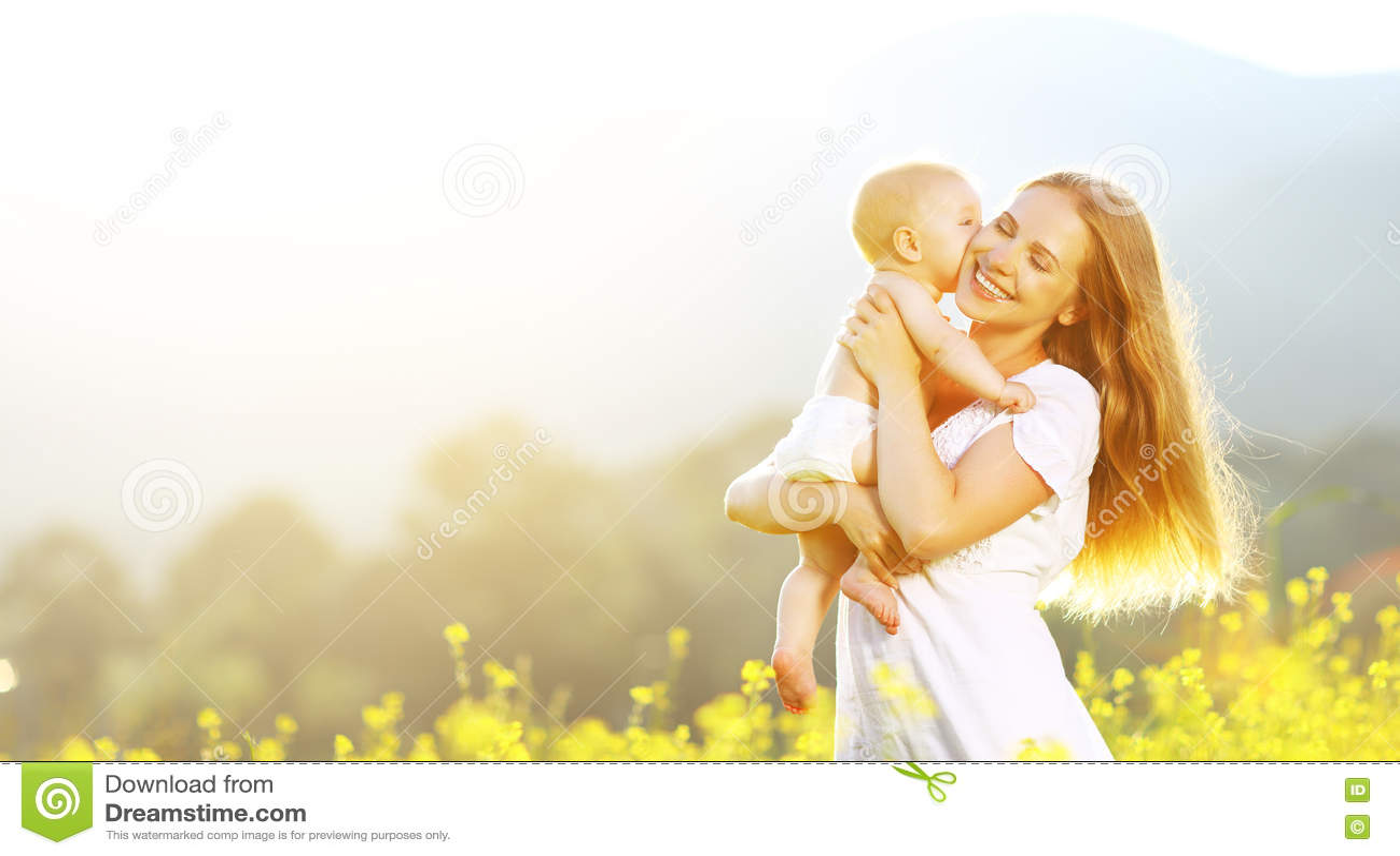 Glückliche Familienmutter und Babyumarmen und -kuß im Sommer auf natur
