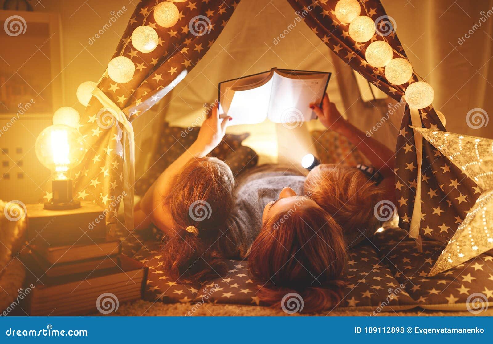 Glückliche Familienmutter und -kinder, die ein Buch im Zelt am hom lesen
