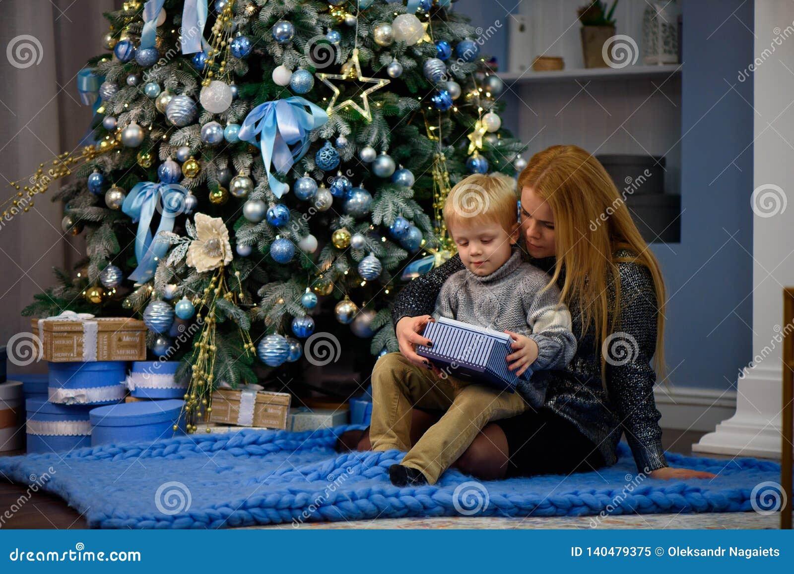 Glückliche Familienmutter und Sohn des Babys kleiner, der nach Hause an den Weihnachtsfeiertagen spielt Neues Jahr ` s Feiertage