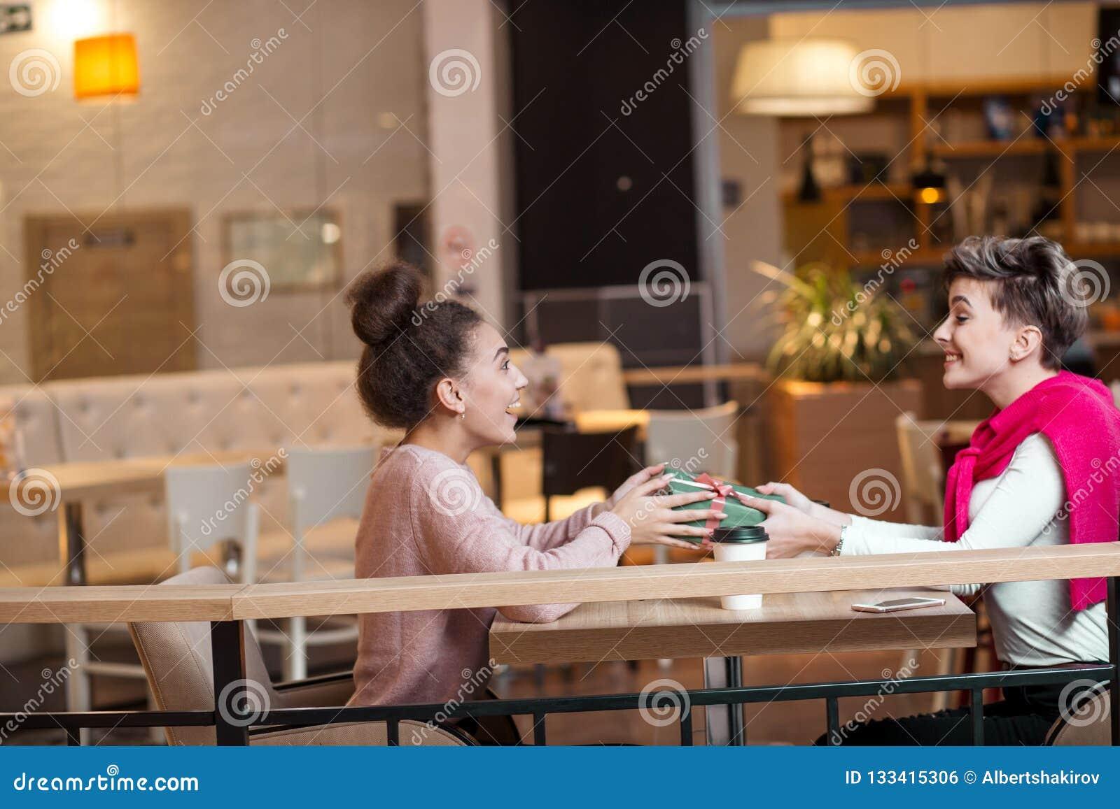 Glückliche Frau beglückwünscht ihre Freundin mit Präsentkarton beim Sitzen am Café