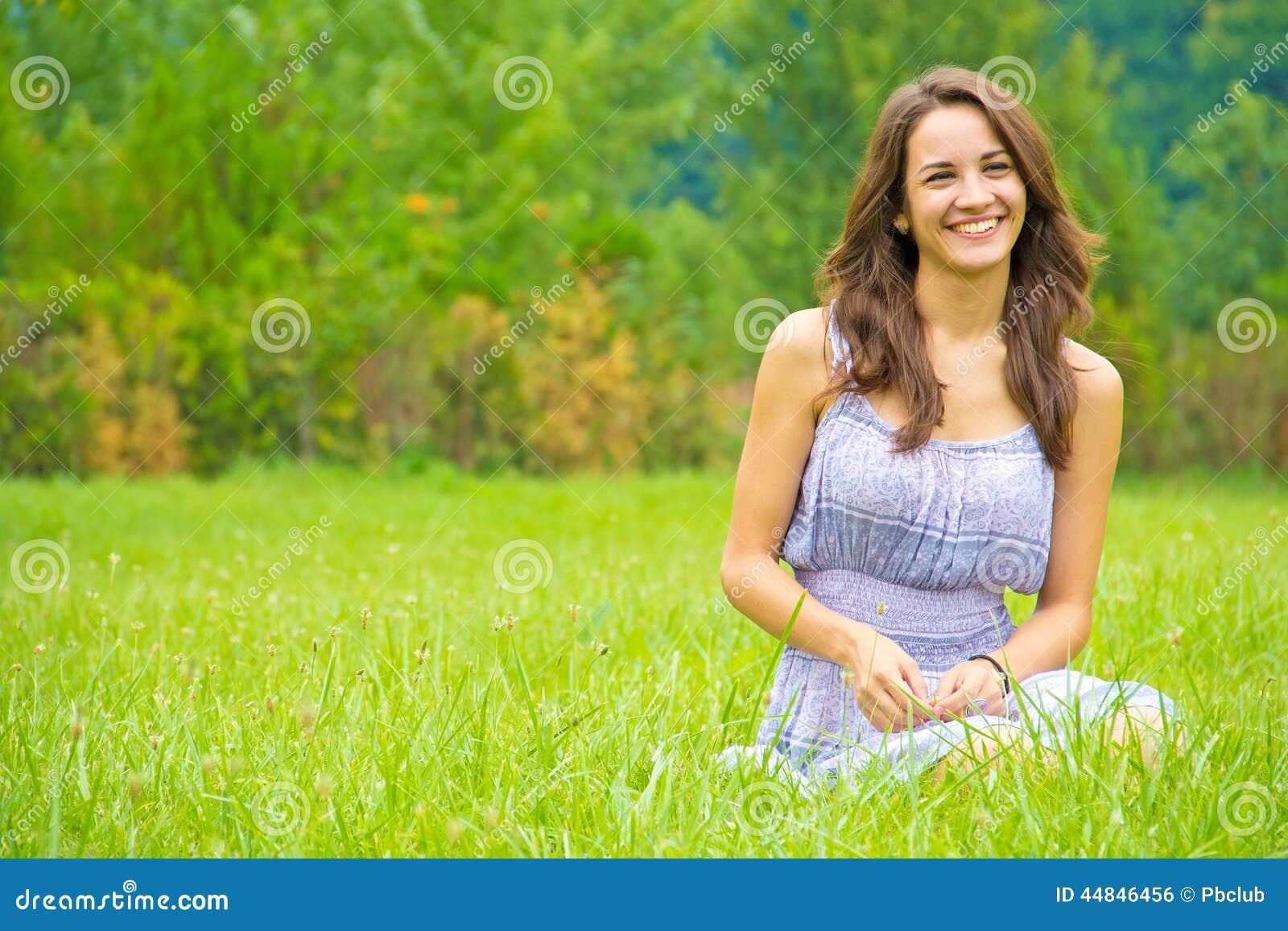 Glückliche Frau, die auf Gras sitzt