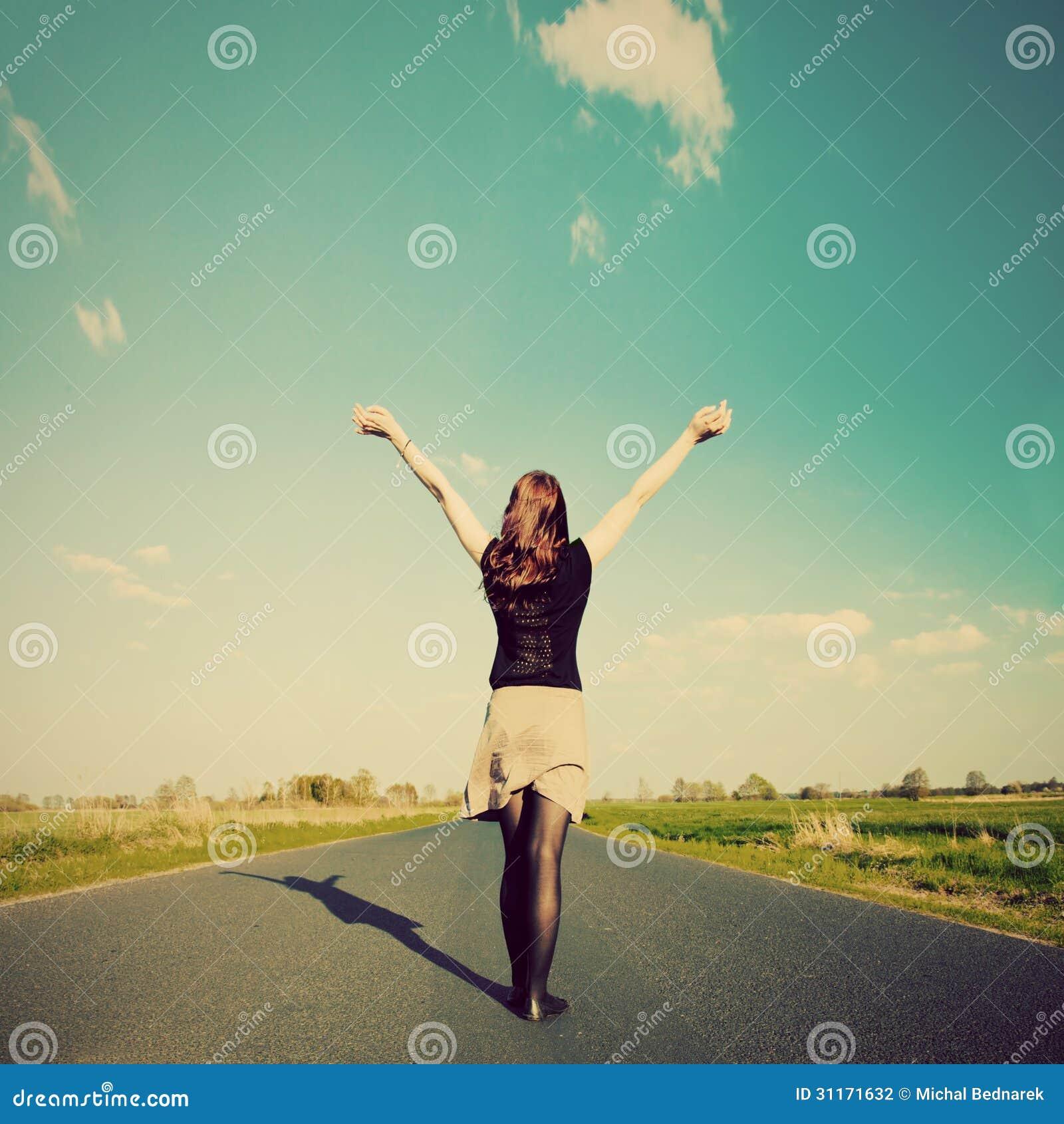 Glückliche Frau, die auf leerer Straße steht. Retro- Weinleseart