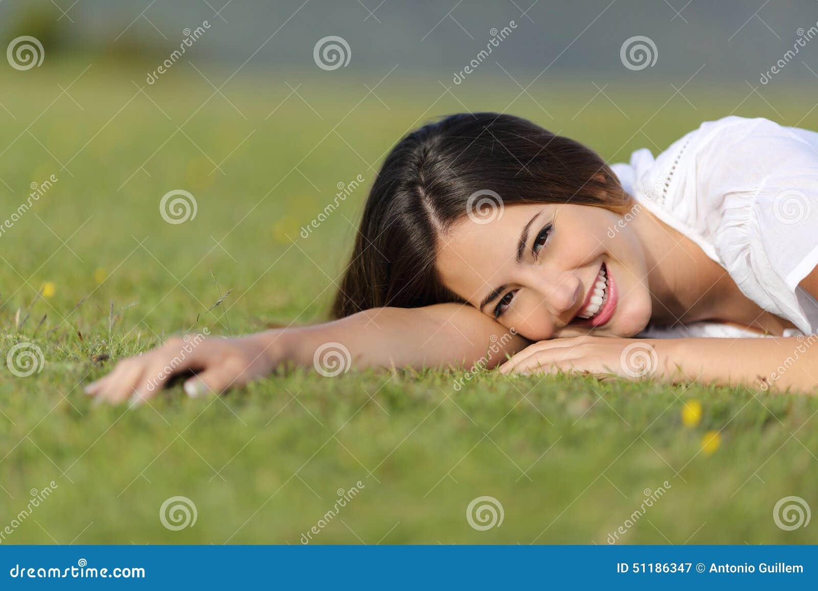 39c1767585 Glückliche Frau, die betrachtet Kamera lächelt und stillsteht entspannt auf  dem Gras im Berg oder ein Park