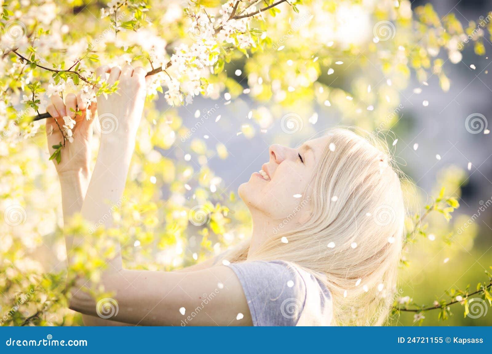 Glückliche Frau, die Frühling, Natur, fallendes Blumenblatt genießt