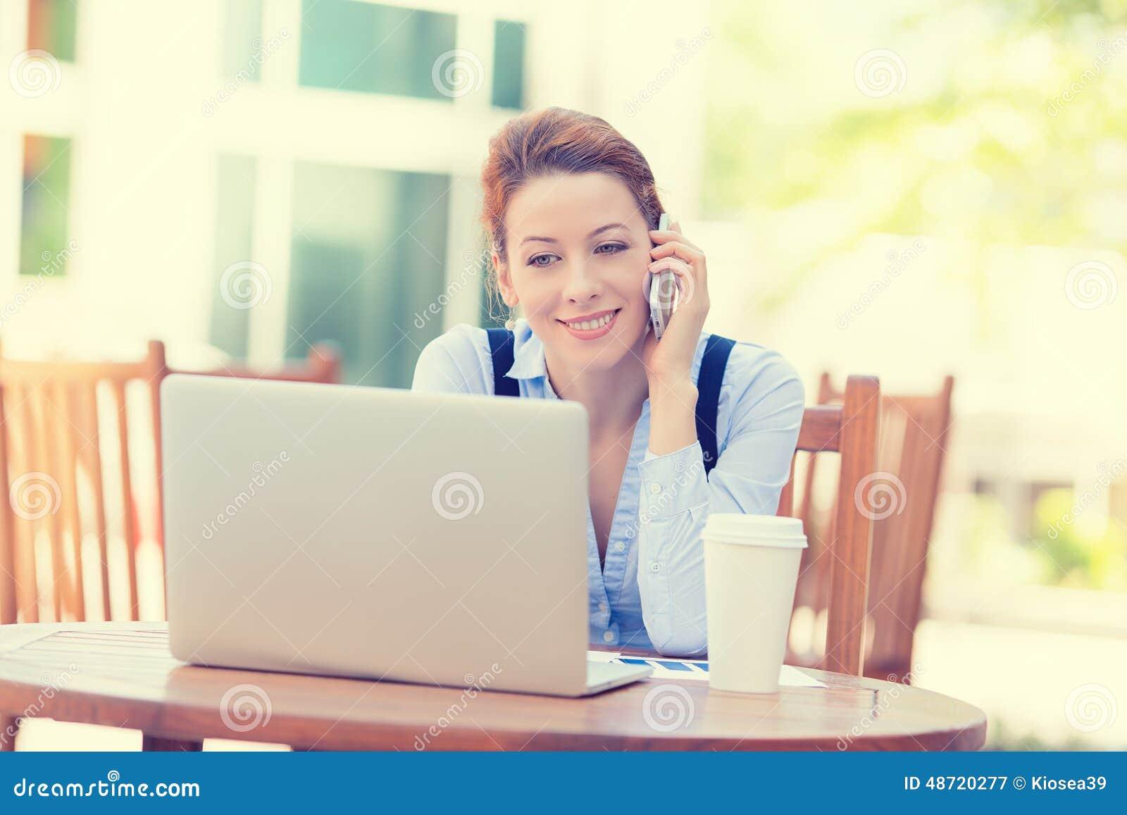 Glückliche Frau, die am Handy arbeitet an Computerlaptop spricht