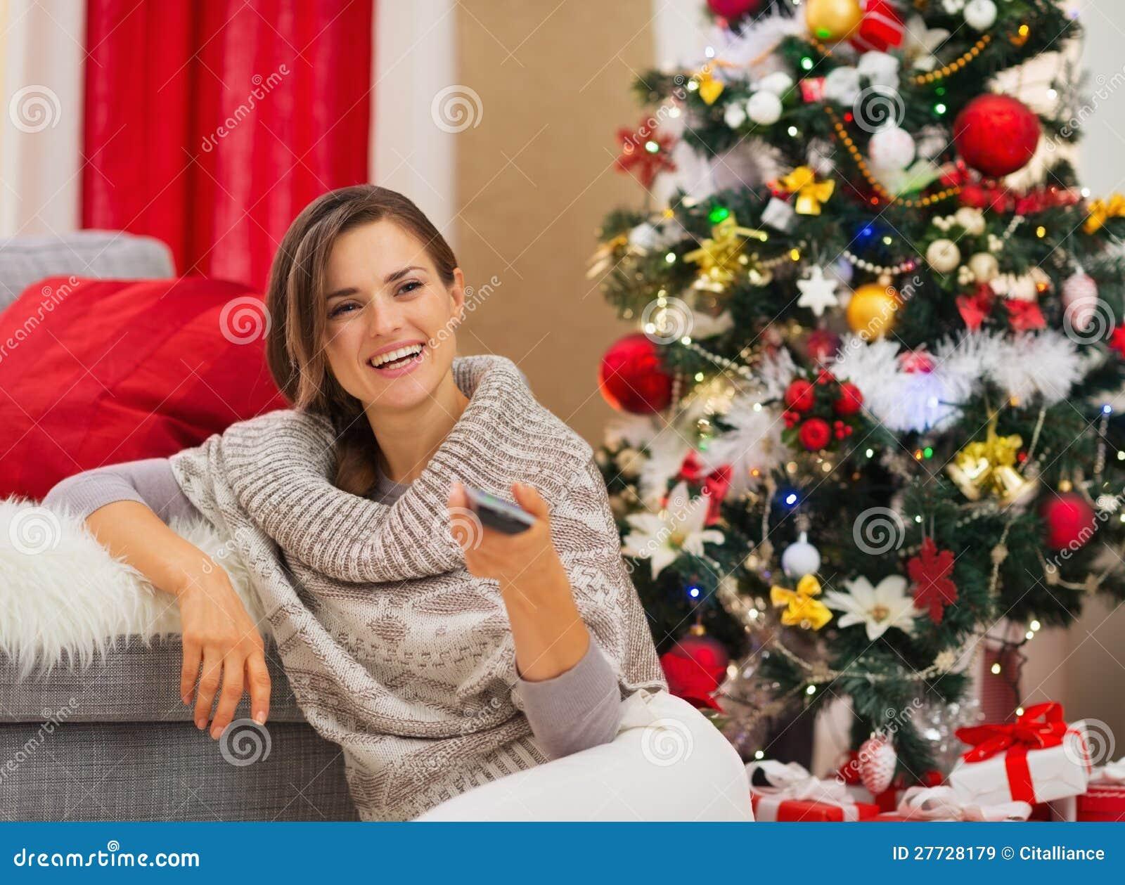 Glückliche Frau, die Nahe Weihnachtsbaum fernsieht