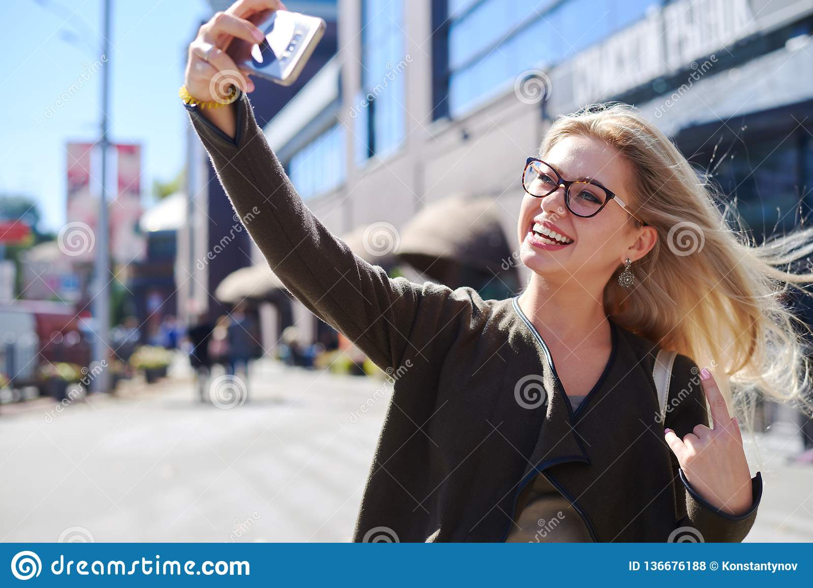 Glückliche Frau, die selfie unter Verwendung der beweglichen Kamera in der Stadt nimmt