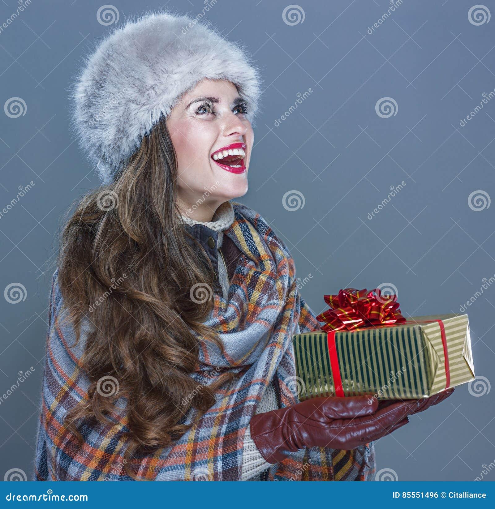Glückliche Frau lokalisiert auf dem kalten blauen Hintergrund, der Präsentkarton gibt