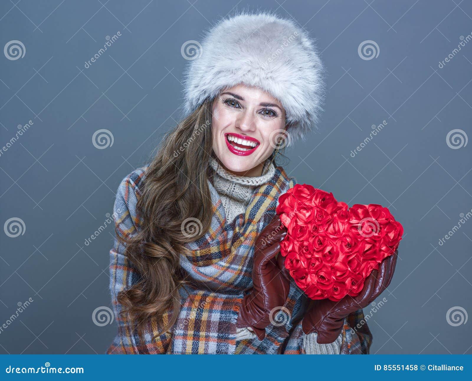 Glückliche Frau lokalisiert auf dem kalten blauen Hintergrund, der rotes Herz zeigt