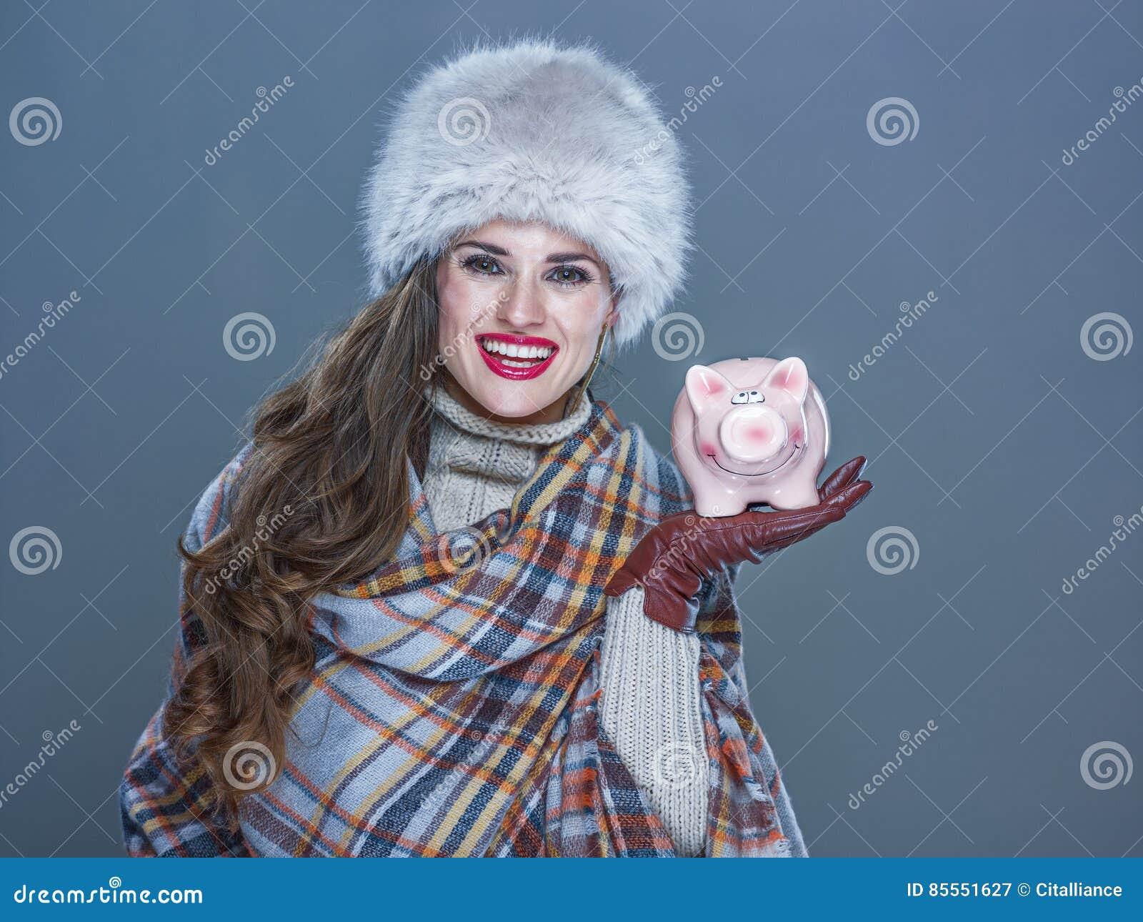Glückliche Frau lokalisiert auf dem kalten blauen Hintergrund, der Sparschwein zeigt