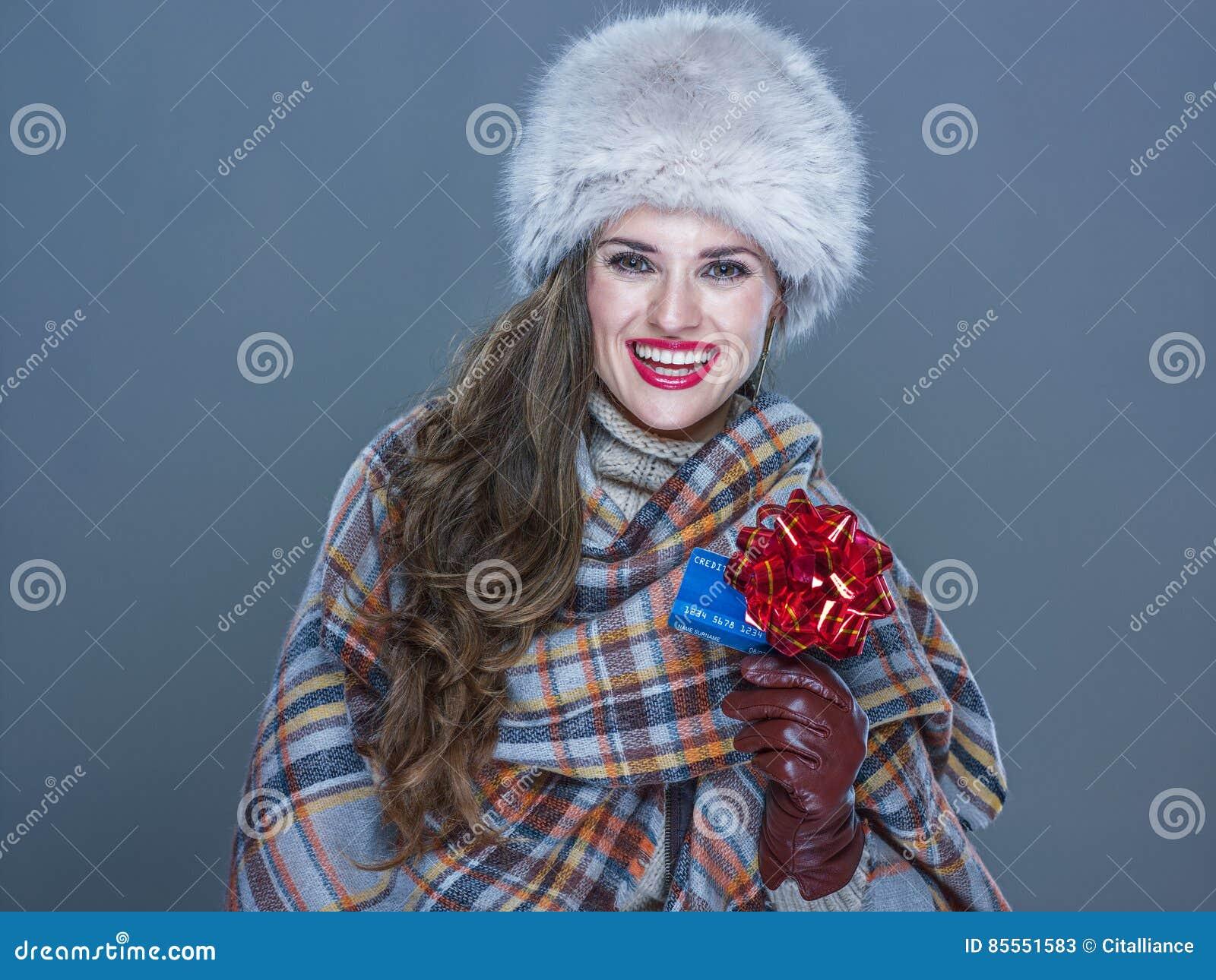 Glückliche Frau lokalisiert auf kalter blauer darstellender Kreditkarte mit rotem r