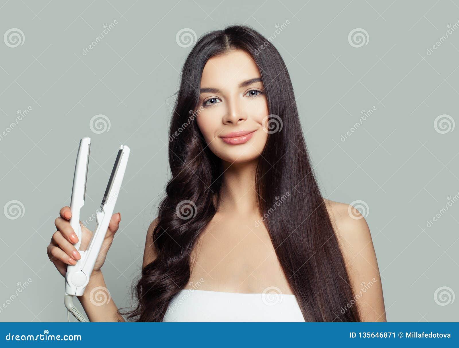Glückliche Frau mit dem geraden Haar und dem gelockten Haar unter Verwendung des Haarstreckers Geraderichtende gesunde brunette F