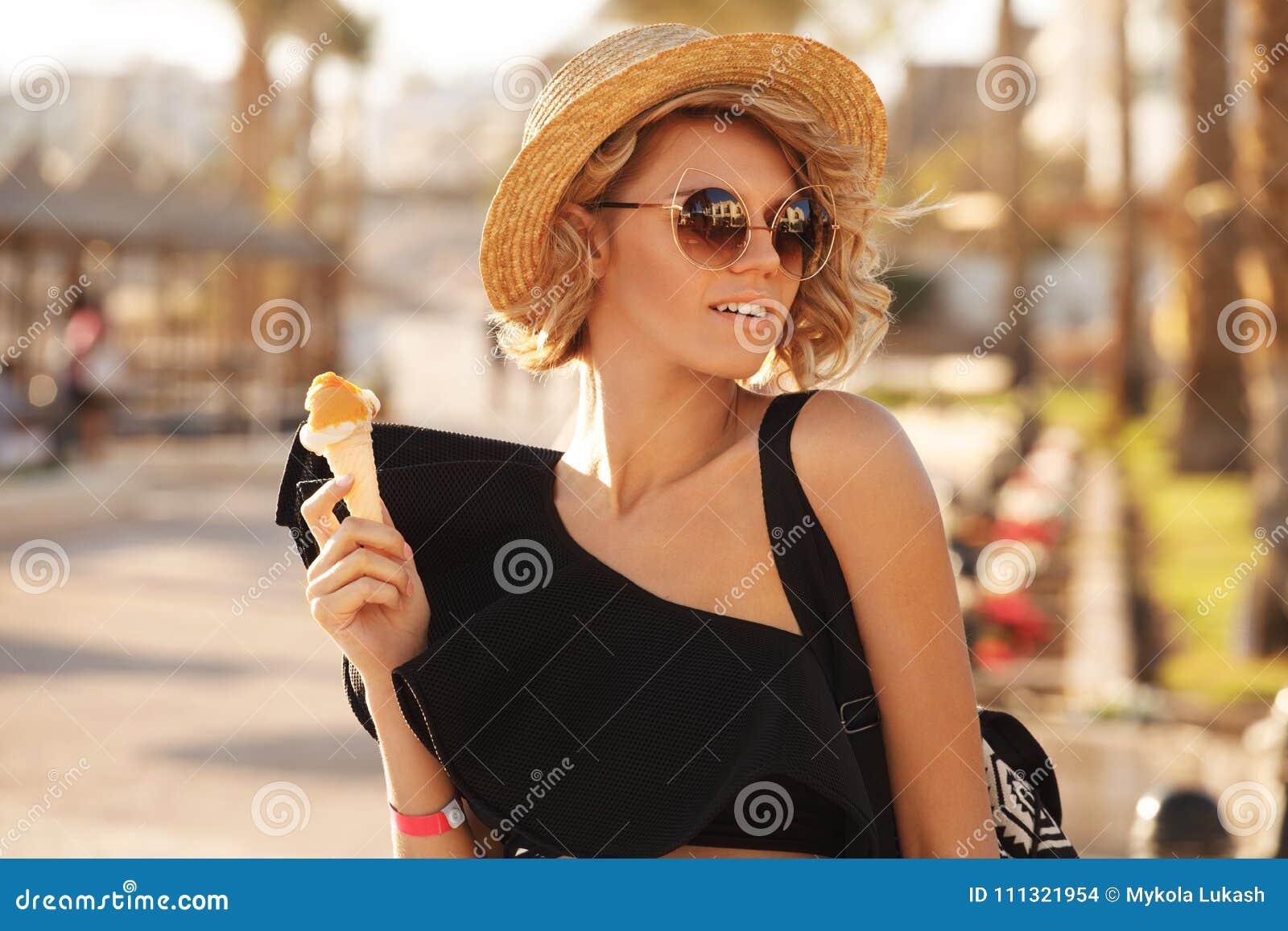 Glückliche Frau mit tragender Sonnenbrille der Eiscreme und der Strandhut, der Sommerspaß während der Reisefeiertage hat, machen