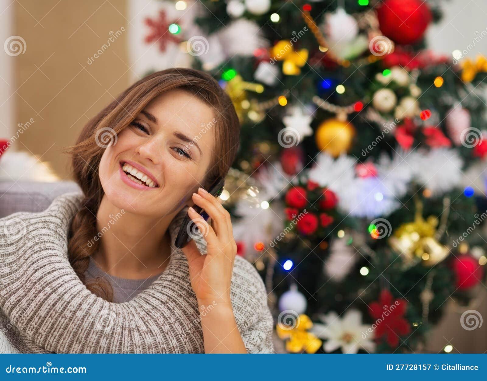 Glückliche Frau nahe dem Weihnachtsbaum, der Telefonaufruf bildet