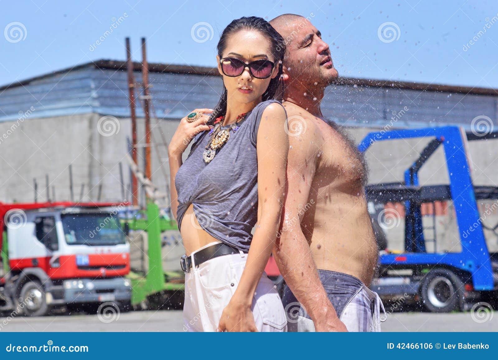 Glückliche Frau, schönes schwarzes Haar, nasse Kleidung, hinterer Mann, LKW