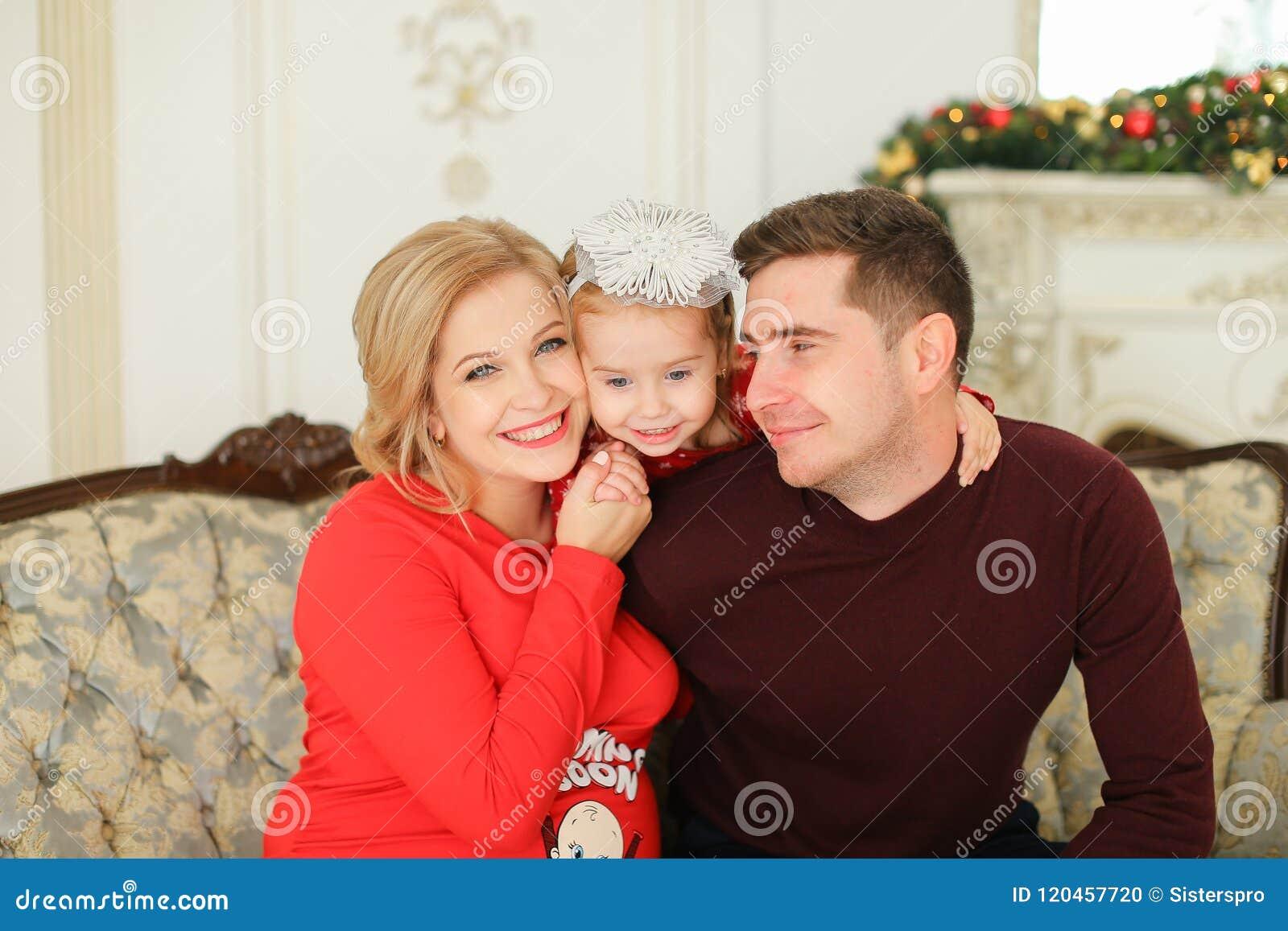 Glückliche Frau und Mann, die mit nahem verziertem Kamin der kleinen Tochter sitzt