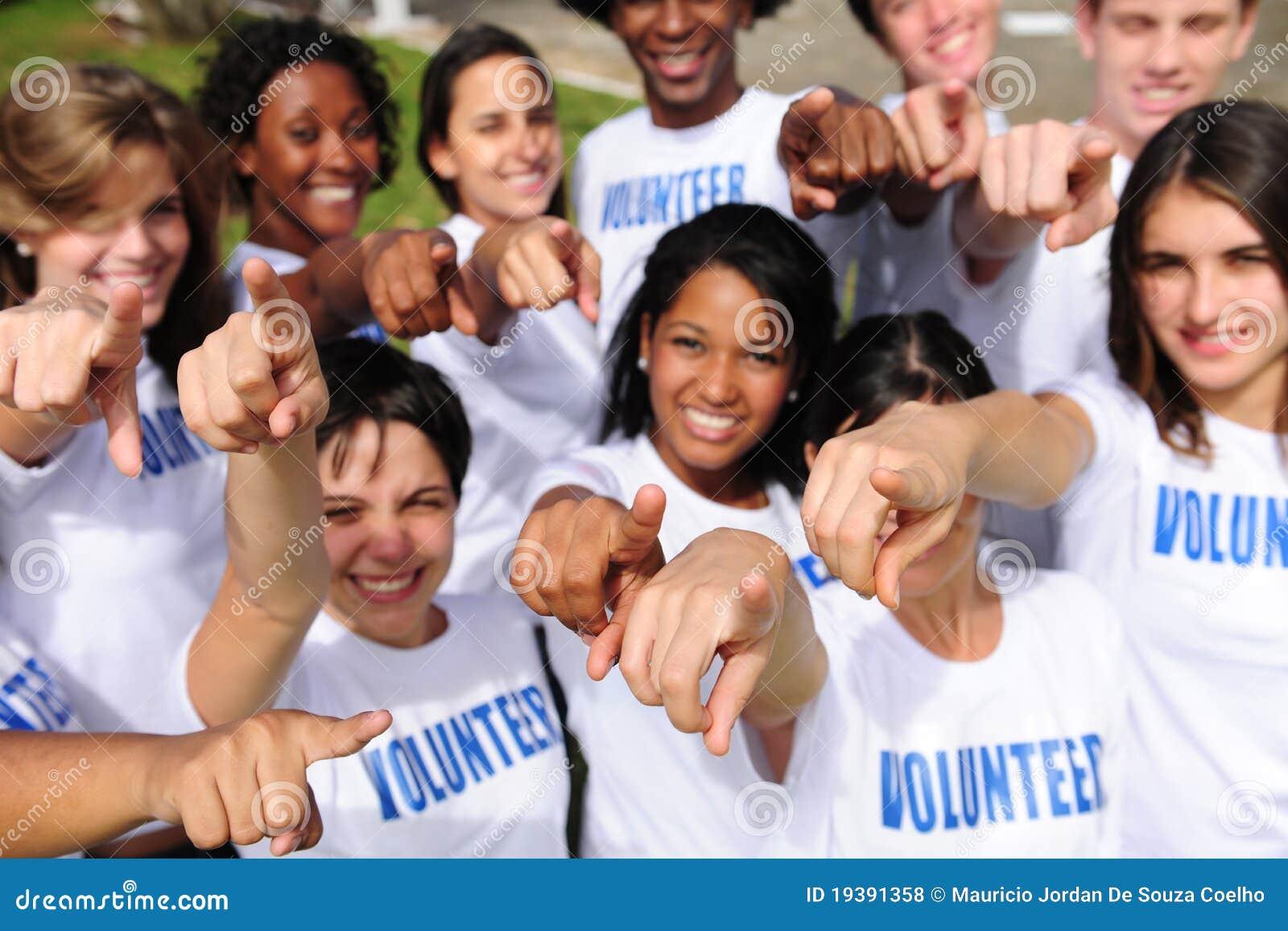 Glückliche freiwillige Gruppe, die in Richtung zur Kamera zeigt