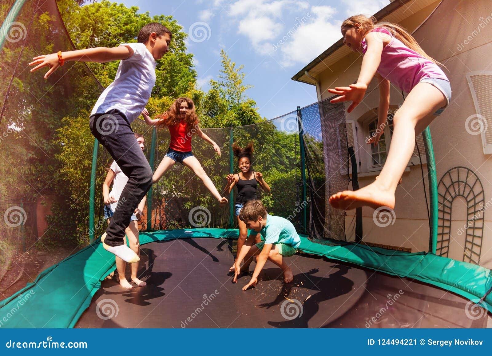 Glückliche Freunde, die auf die Trampoline im Sommer springen