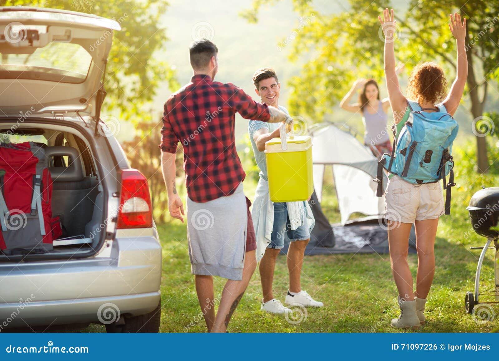 Glückliche Freunde, die Auto für Camping-Ausflug auspacken