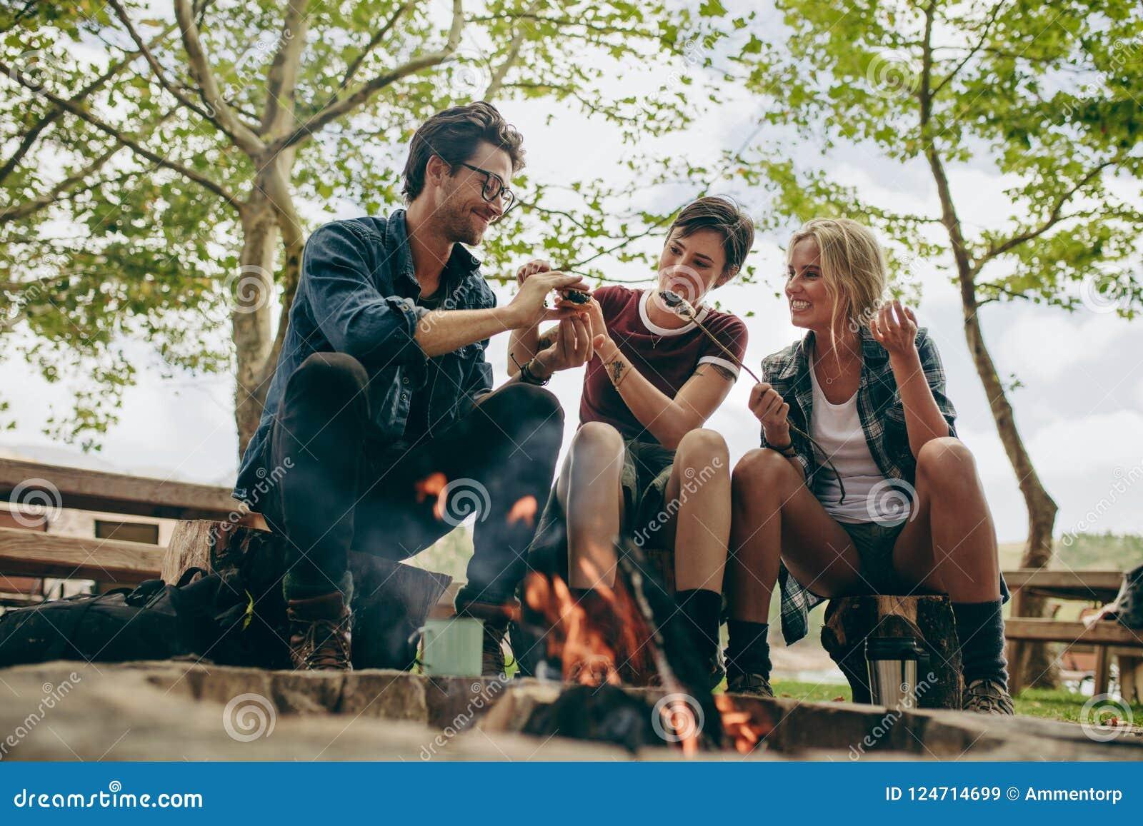 Glückliche Freunde im Urlaub, die in der Landschaft kampieren